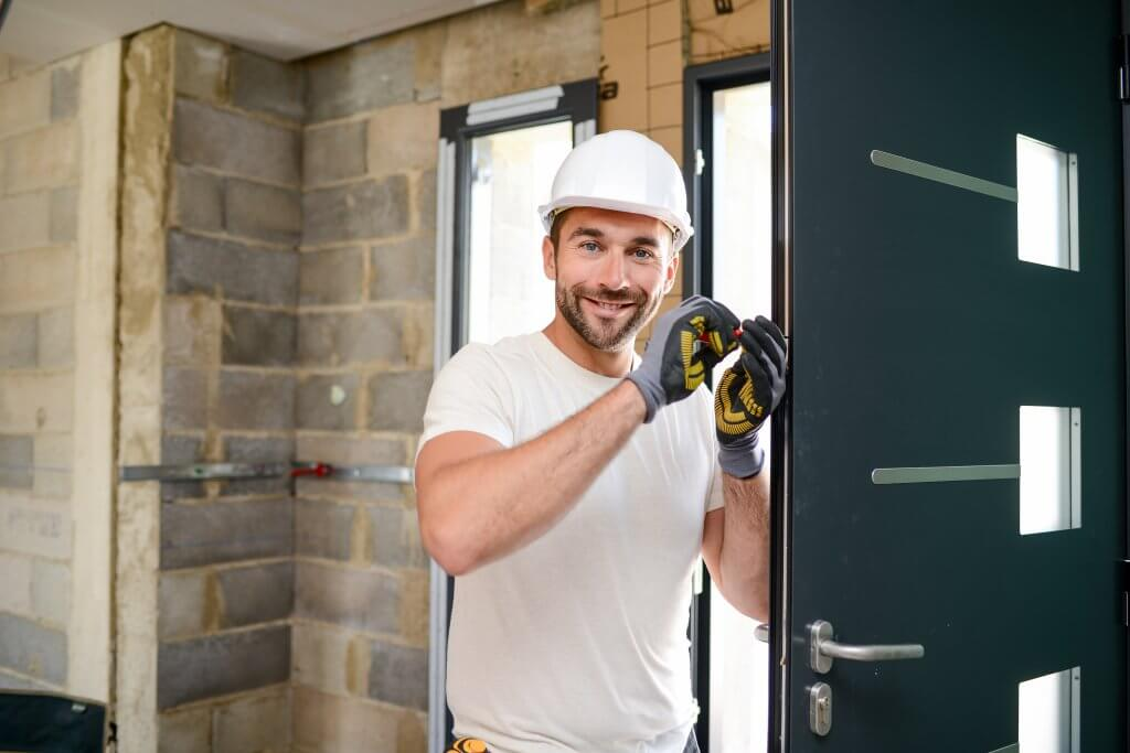 handsome young man installing door in a new house construction site